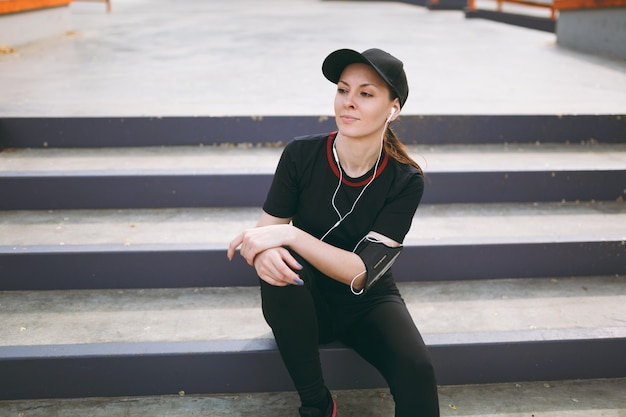 Young athletic beautiful woman in black uniform, cap with headphones listening to music resting and sitting before or after running, training on stairs in city park outdoors