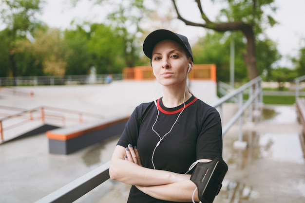 Young athletic beautiful woman in black uniform, cap with headphones listening to music, standing keeping hands folded before or after running, training in city park outdoors