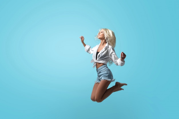 Young athletic blond girl in summer clothes high jumping on an isolated blue space in studio