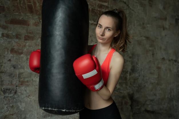 Молодая спортивная женщина-боксер в тренажерном зале рядом с пробивной грушей Premium Фотографии
