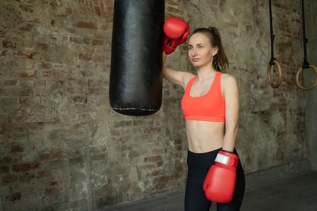Молодая спортивная женщина-боксер в тренажерном зале рядом с пробивной грушей