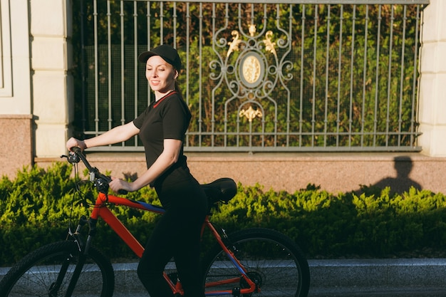 검은색 제복을 입은 젊고 강한 브루네트 여성, 모자는 봄이나 여름 화창한 날 야외에서 주황색 요소가 있는 검은색 자전거를 타고 길을 멈춥니다. 피트 니스, 스포츠, 건강 한 라이프 스타일 개념입니다.