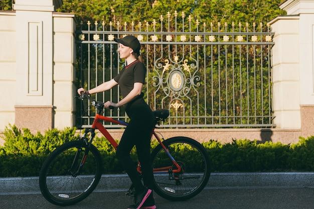 黒い制服を着た若い運動ブルネットの強い女性、春または夏の晴れた日に屋外でオレンジ色の要素を持つ黒い自転車で道路に乗るのをやめます。フィットネス、スポーツ、健康的なライフスタイルのコンセプト。