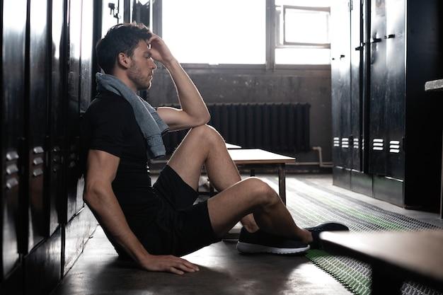 운동 후 휴식을 취하는 어두운 체육관 라커룸에 혼자 앉아 있는 젊은 운동 백인 남자.