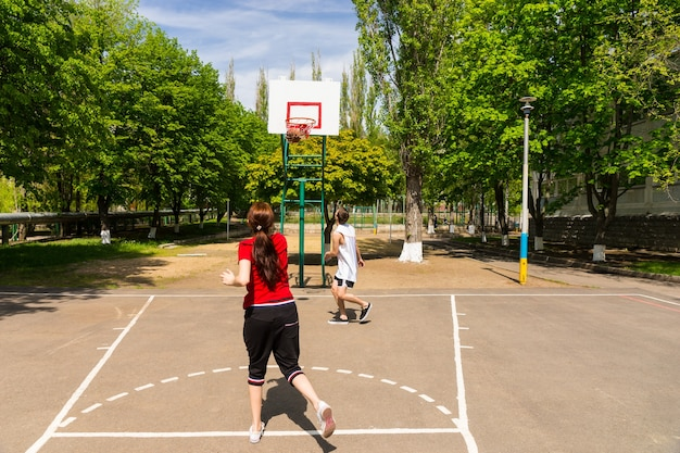 一緒にバスケットボールをしている若い運動カップル-緑豊かな緑の公園の屋外コートで女性がキーの上からショットを撮るのを見ている男性