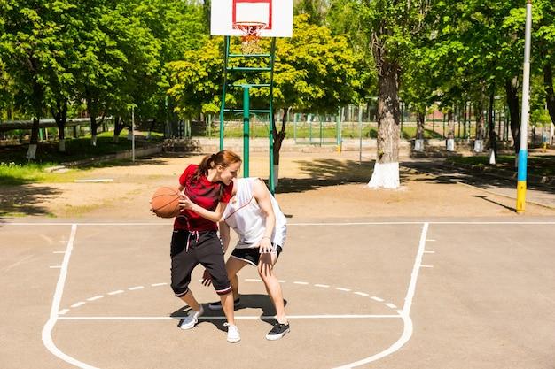 緑豊かな緑の公園の屋外コートで一緒にバスケットボールをする若い運動カップル