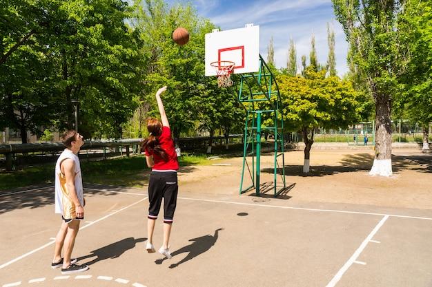 一緒にバスケットボールをする若い運動カップル-緑豊かな緑豊かな公園の屋外コートでショットを撮る女性