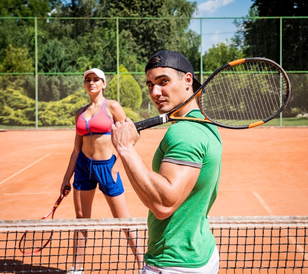 Young athletic couple playing tennis on the court