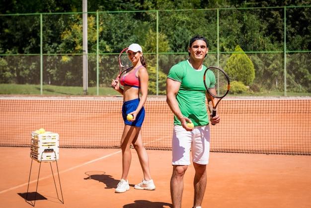 コートでテニスをしている若い運動選手のカップル。