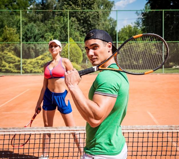 コートでテニスをして運動の若いカップル