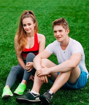 Young athletic couple sitting on the grass