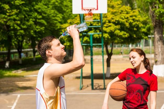 농구 코트에서 상쾌한 휴식을 취하는 젊은 운동 커플, 남자가 얼굴에 물병을 비우는 모습을 바라보는 여자