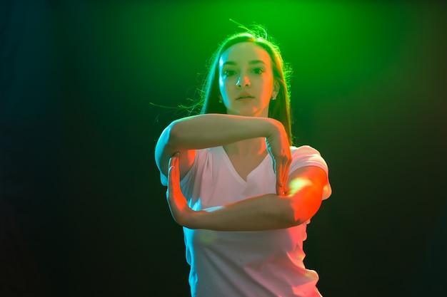 Young athletic female dancing street dance in studio.