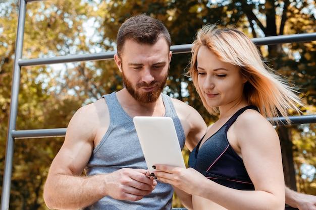運動少女とあごひげを生やした男は秋の日に公園でフィットネス運動をしながらタブレットpcでインターネットを閲覧します。
