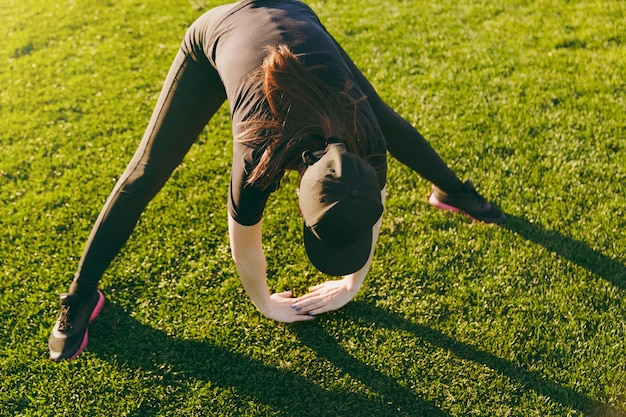 Young athletic girl in black uniform, cap doing sport exercises, warm-up, stretching before running on green lawn in golf course park outdoors on sunny summer day. fitness, healthy lifestyle concept.