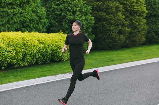 Young athletic girl in black uniform and cap training, doing sport exercises, running, looking straight on path in city park outdoors on spring or summer sunny day. fitness, healthy lifestyle concept.