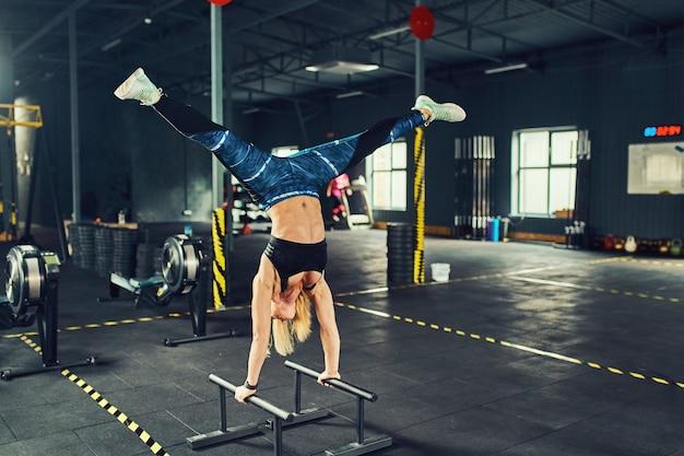 現代のジムでストレッチ体操をしている若い運動少女。