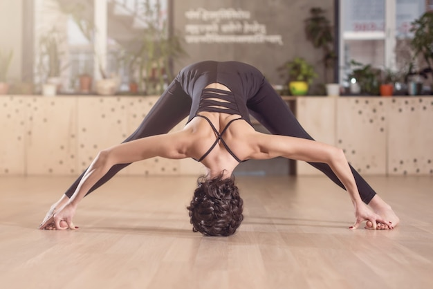 Young athletic girl doing stretching yoga exercises. standing with barefoot legs apart and hands head touching the floor