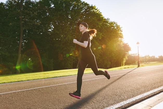 春や夏の晴れた日に屋外の都市公園の小道をまっすぐ見ながら、スポーツエクササイズ、ランニング、黒のユニフォームとキャップのトレーニングをしている若い運動少女。フィットネス、健康的なライフスタイルのコンセプト。