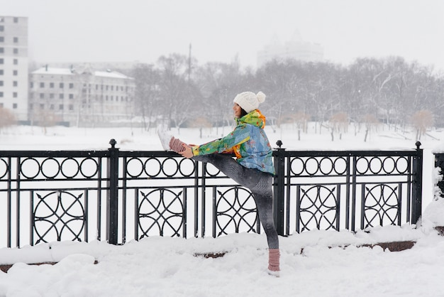 A young athletic girl is warming up before running on frosty day. fitness, running.