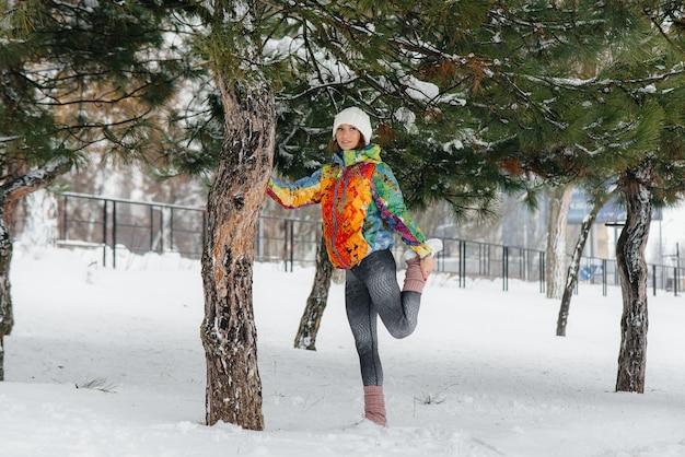 運動の少女は、凍るような日に実行する前にウォーミングアップします。フィットネス、ランニング