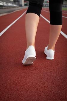 トレッドミルトレッドミルで生産的なフィットネストレーニングマラソンの準備をしている白いスニーカーランナーの若い運動少女の脚。市の競技場で運動服を着た女性。コピースペースのある画像