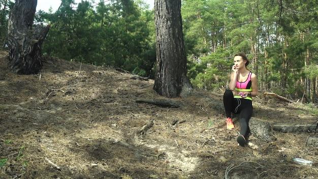 音楽を聴いて森の中で逃げる若い運動少女