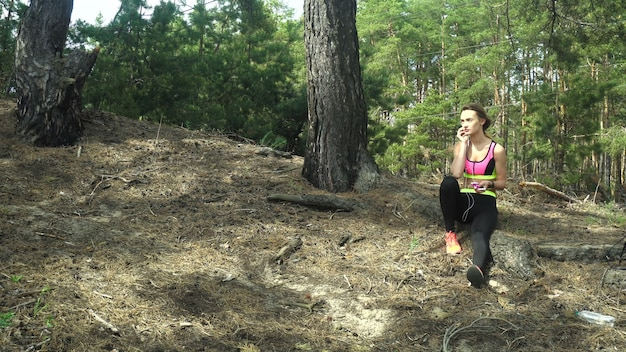 Young athletic girl listening music and running away in the wood