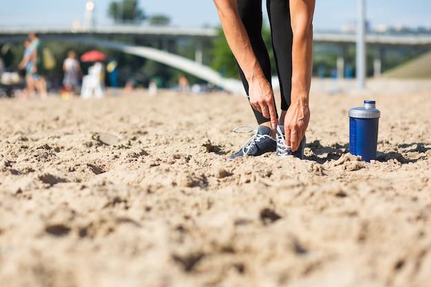 ビーチで靴紐を結ぶ若い運動少女。テキスト用のスペース