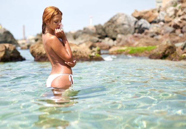 海沿いのスリムな体を持つ若い運動少女