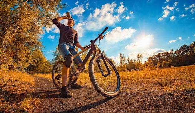 Молодой спортивный парень в черной футболке и бейсболке на спортивном велосипеде пьет воду из шейкера в осеннем пейзаже