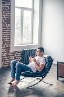 흰색 티 셔츠와 맨발, 안락의 자에 방에 앉아 모닝 커피를 마시고 웃 고있는 젊은 체육 남자.
