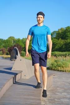 Молодой спортивный парень в спортивной одежде, упражнения на открытом воздухе в солнечный летний день