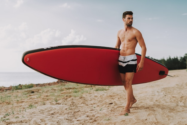 Young athletic guy with surf standing on beach.