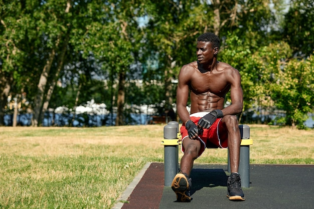 遊び場の公園で腕立て伏せをしている若い運動の半裸の男。フィットネスと屋外運動セレクティブフォーカス、クローズアップ。