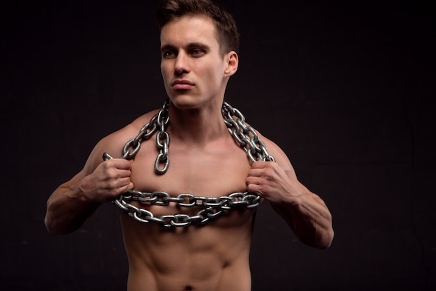 A young athletic handsome man with chains around his neck. photo on a dark background
