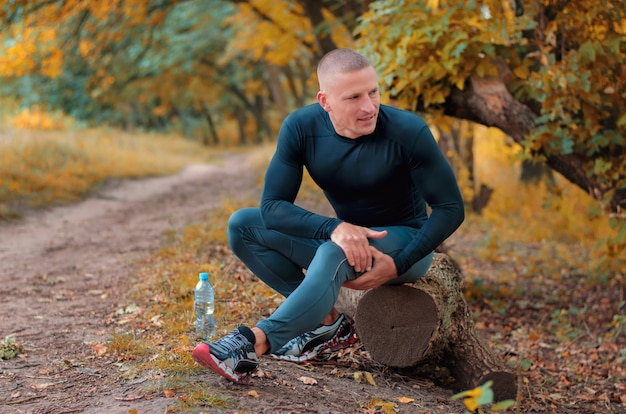 A young athletic jogger in black sportswears and sneakers sits on a log, is in pain and holding a hip with his hands after cramping