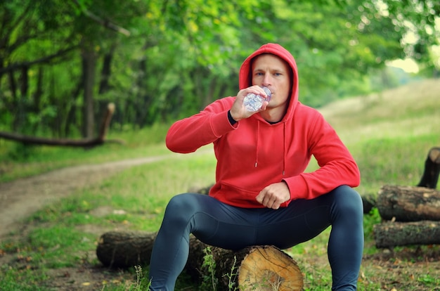 A young athletic  jogger in a red  jacket with a hood and black  leggings sits on a log and drink water from a bottle after running on a green spring forest.