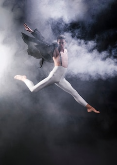 Young athletic male jumping with extended legs and hands near smoke