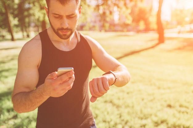 トレーニング後の若い運動男。ハンサムな若い筋肉男はタンパク質を飲みます。ブレンダーからスポーツ栄養シェイクを飲む魅力的なアスレチック上半身裸スポーツマン。