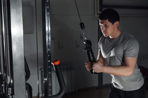 ジムでブロックエクササイザーの上腕三頭筋の運動をしている若い運動男。