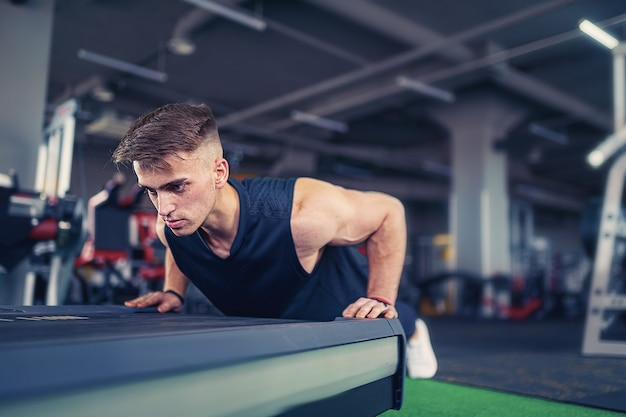 Young athletic man doing push-ups in gym