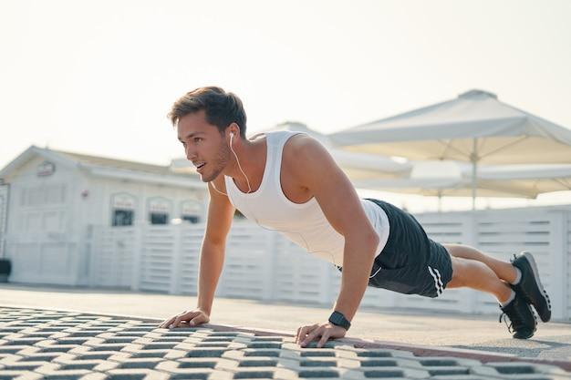 Молодой спортивный мужчина делает отжимания