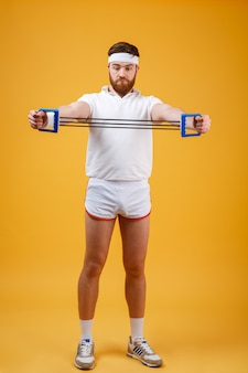 Young athletic man exercising with chest expander or resistance band