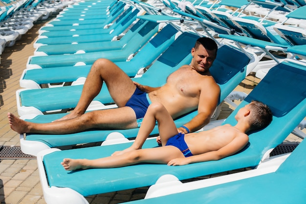 A young athletic man and his son are smiling happily and sunbathing on a sun lounger on a sunny day. happy vacation vacation. summer holidays and tourism.