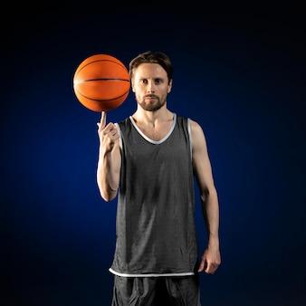 Молодой спортивный человек, держащий баскетбол