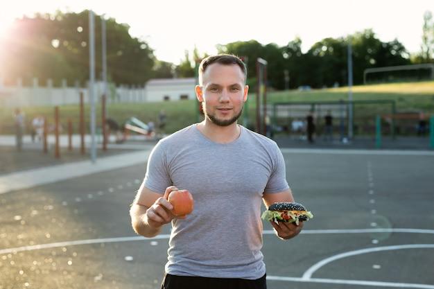 Tシャツを着た若いアスリートの男がスタジアムの背景にハンバーガーとリンゴを持っています。健康と不健康な食べ物の選択肢です。