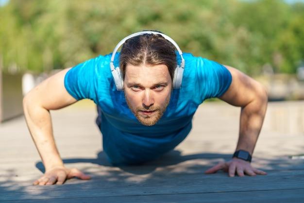 Молодой спортивный мужчина в наушниках делает отжимания во время тренировки на открытом воздухе