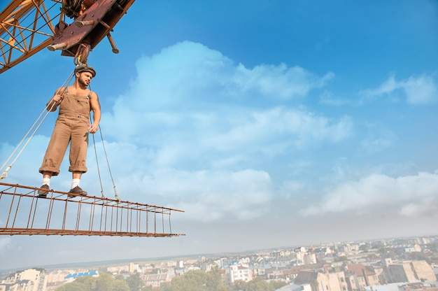 高い上に建設に立って目をそらしている作業服と帽子の若い運動選手。街並みと背景の青い空。空中で都市の上に男性と一緒に建設を保持している大きな建物のクレーン。