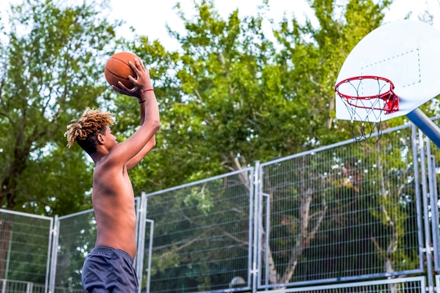 Young and athletic man is suspended in the air with a basketball playing on the court